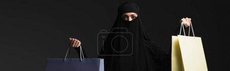 Photo pour Femme arabe en niqab noir avec sacs à provisions multicolores isolés sur noir, bannière - image libre de droit