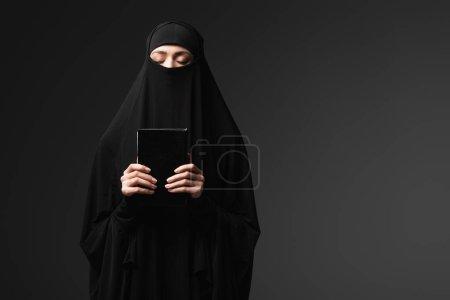 Photo pour Femme musulmane tenant koran tout en priant isolé sur noir - image libre de droit