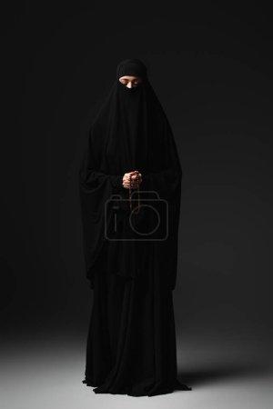 Photo pour Vue pleine longueur de religieuse musulmane en niqab noir et abaya priant avec chapelet sur fond noir - image libre de droit