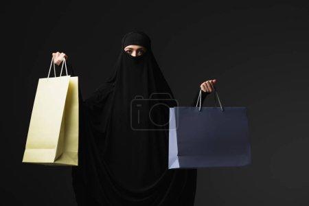 Photo pour Nonne musulmane en niqab noir tenant des sacs à provisions multicolores isolés sur noir - image libre de droit