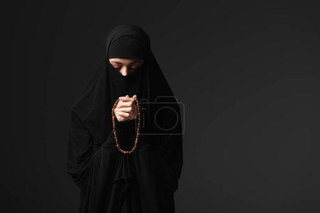 Photo pour Religieuse musulmane en vêtements traditionnels noirs priant avec chapelet isolé sur noir - image libre de droit
