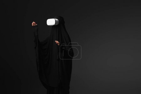 Photo for Muslim nun in black abaya gesturing in vr headset isolated on black - Royalty Free Image