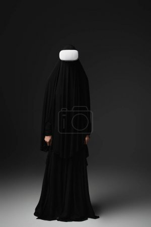 Photo for Full length view of muslim nun in black abaya and vr headset on black background - Royalty Free Image