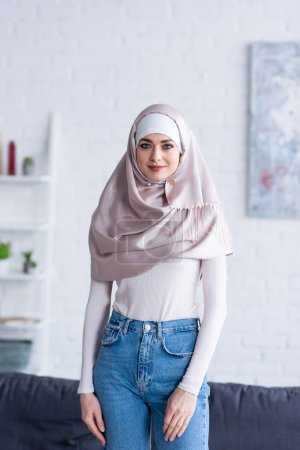 Photo for Young arabian woman in hijab and jeans looking at camera at home - Royalty Free Image