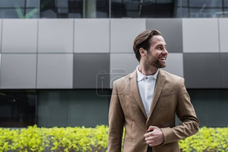 cheerful businessman unbuttoning blazer and looking away outside