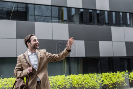 Photo for Cheerful businessman with leather bag waving hand outside - Royalty Free Image