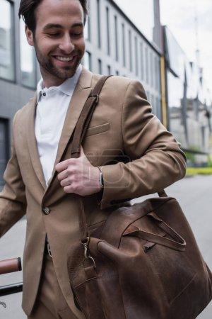 glücklicher Geschäftsmann im Anzug mit Ledertasche und lächelnd draußen