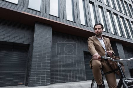 young businessman in suit with leather bag riding bicycle outside