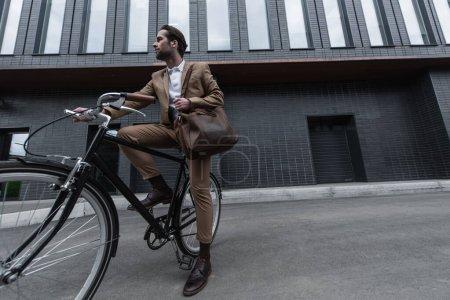Photo pour Pleine longueur de jeune homme d'affaires en tenue formelle avec sac en cuir vélo d'équitation à l'extérieur - image libre de droit