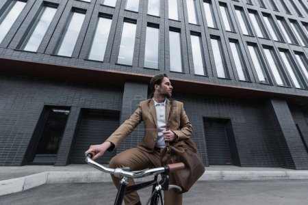joven hombre de negocios en ropa formal con bolsa de cuero marrón montar en bicicleta fuera