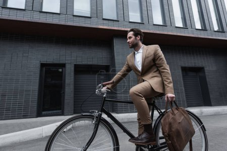 Photo for Young businessman in formal wear holding leather brown bag and riding bicycle outside - Royalty Free Image