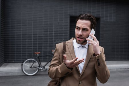 Photo pour Stressé jeune homme d'affaires en tenue formelle parler sur smartphone à l'extérieur - image libre de droit
