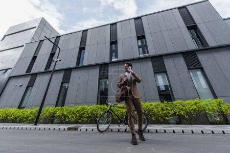 Photo pour Pleine longueur de heureux jeune homme d'affaires en tenue formelle parlant sur téléphone portable près de l'immeuble - image libre de droit
