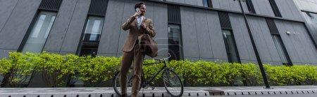Foto de Longitud completa de joven empresario feliz en ropa formal hablando en el teléfono celular cerca del edificio, pancarta - Imagen libre de derechos