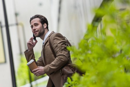 Photo for Smiling man in formal wear talking on cellphone and holding paper cup near blurred plant - Royalty Free Image