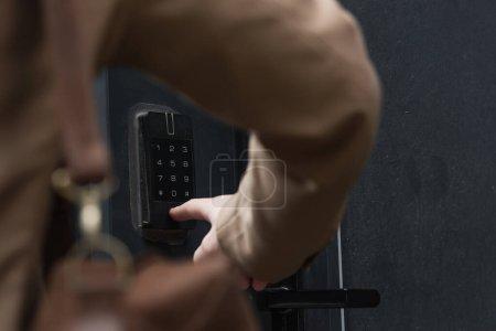 vista parcial del hombre pulsando el botón en el teclado del intercomunicador