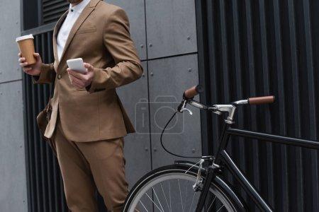 Ausgeschnittene Ansicht von Geschäftsmann mit Pappbecher und Smartphone in der Nähe von Fahrrad