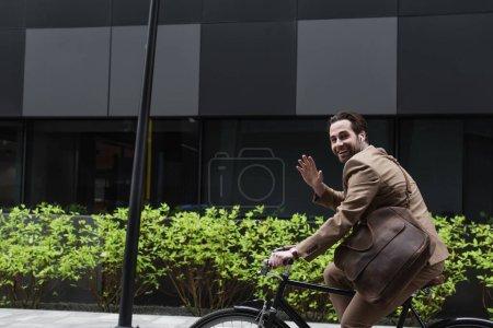 Photo pour Homme d'affaires heureux dans les écouteurs à vélo et agitant la main près du bâtiment et des plantes - image libre de droit