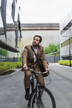 Photo for Full length of businessman in earphones riding bicycle near buildings - Royalty Free Image