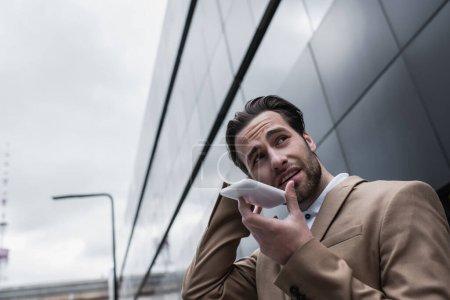 Photo pour Homme d'affaires barbu enregistrement message vocal sur smartphone à l'extérieur - image libre de droit