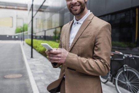 Foto de Vista recortada del hombre de negocios barbudo sonriendo mientras sostiene el teléfono inteligente fuera - Imagen libre de derechos