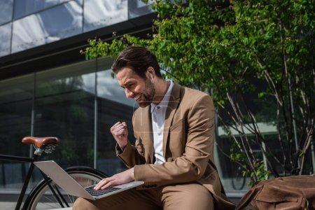 podekscytowany biznesmen w słuchawkach za pomocą laptopa podczas siedzenia na ławce