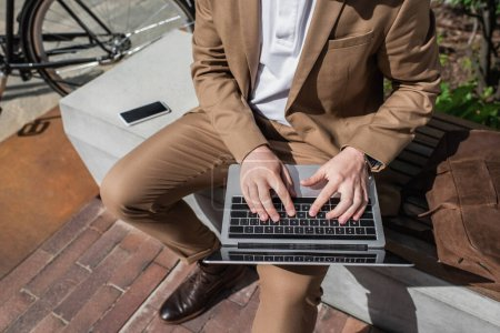 cropped view of businessman typing on laptop while sitting on bench
