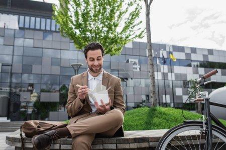 Photo pour Heureux homme d'affaires en costume tenant boîte en carton avec de la nourriture asiatique et baguettes près de vélo - image libre de droit