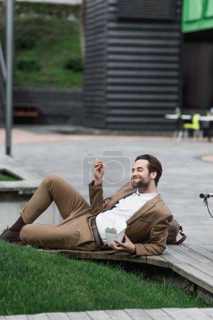 glücklicher Geschäftsmann mit Pappschachtel mit asiatischem Essen und Essstäbchen im Liegen im Gras
