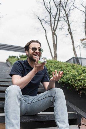Photo pour Homme joyeux en lunettes de soleil et polo enregistrement message vocal sur téléphone portable à l'extérieur - image libre de droit