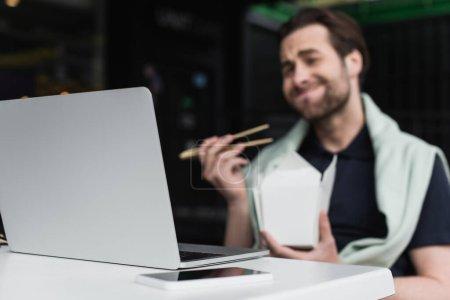 Photo pour Homme flou en polo et sweat-shirt tenant baguettes et boîte en carton tout en regardant ordinateur portable près du smartphone - image libre de droit