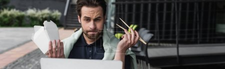 bearded man in polo shirt and sweatshirt holding chopsticks and carboard box while looking at laptop in outdoor cafe, banner