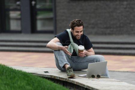 Photo pour Homme gai en polo et sweat-shirt regardant ordinateur portable tout en tenant du café pour aller à l'extérieur - image libre de droit