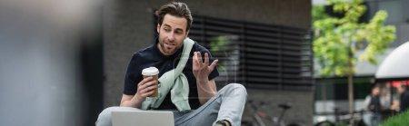 Photo pour Homme barbu gestuelle pendant l'appel vidéo sur ordinateur portable tout en tenant tasse en papier, bannière - image libre de droit
