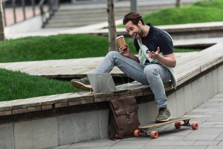 Foto de Hombre alegre en polo y sudadera sosteniendo café para ir y riendo mientras se sienta cerca de longboard y gadgets - Imagen libre de derechos
