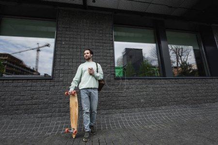 Photo pour Pleine longueur de l'homme en sweat-shirt tenant tasse en papier et longboard à l'extérieur - image libre de droit
