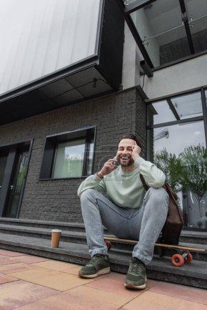 Foto de Longitud completa de hombre feliz en sudadera hablando en el teléfono inteligente cerca de la taza de papel y longboard fuera - Imagen libre de derechos