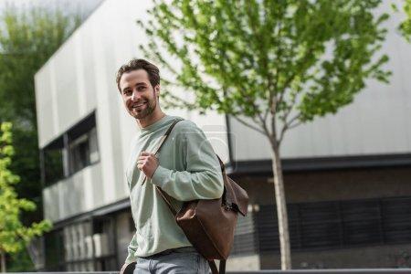 Photo pour Homme barbu souriant en sweat-shirt tenant bracelet en cuir de sac à dos près du bâtiment à l'extérieur - image libre de droit