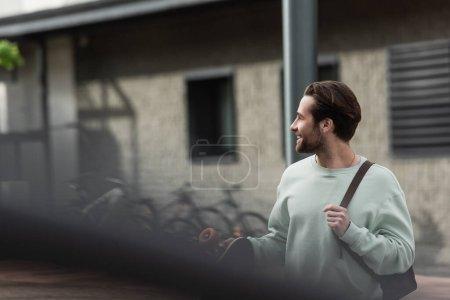 Photo pour Heureux homme barbu en sweat-shirt tenant longboard et bracelet en cuir de sac à dos à l'extérieur - image libre de droit