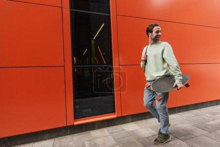 Photo pour Homme gai en sweat-shirt tenant longboard et marchant près du mur orange - image libre de droit
