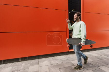 smiling man in sweatshirt holding longboard while pointing with finger near orange wall