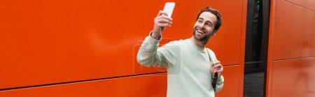 Photo for Cheerful man in sweatshirt taking selfie on smartphone near orange wall, banner - Royalty Free Image