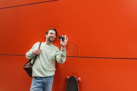 Foto de Hombre alegre en sudadera sosteniendo teléfono inteligente con pantalla en blanco y agitando la mano cerca de la pared naranja - Imagen libre de derechos