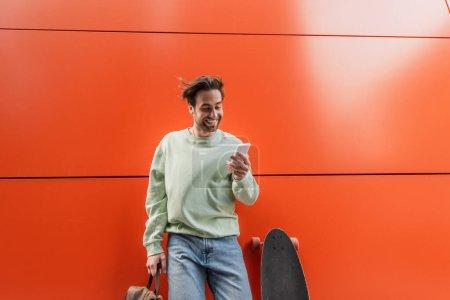 Photo pour Homme gai en sweat-shirt tenant le sac à dos et en utilisant un smartphone près de longboard et mur orange - image libre de droit