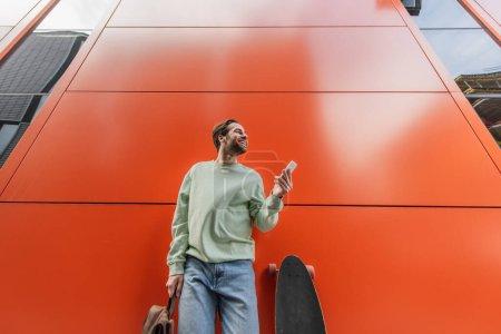 Photo pour Vue à angle bas de l'homme joyeux en sweat-shirt tenant sac à dos et smartphone près de longboard et mur orange - image libre de droit