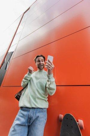 Photo pour Vue à angle bas de l'homme étonné en sweat-shirt tenant smartphone près du mur orange - image libre de droit