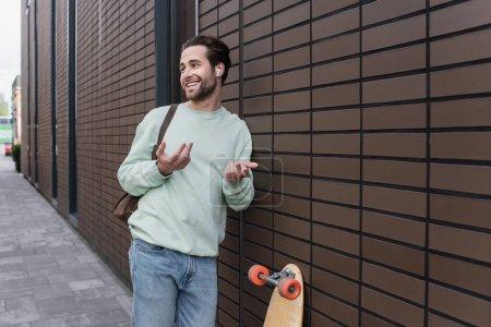 Photo pour Homme heureux en sweat-shirt et écouteurs sans fil parler et gesticuler à l'extérieur - image libre de droit