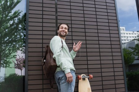 hombre feliz en sudadera y auriculares inalámbricos agitando la mano afuera