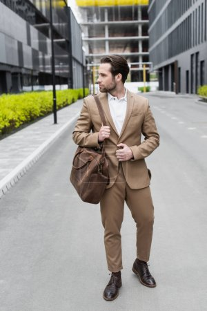 Photo for Full length of bearded businessman in suit holding leather strap of bag outside - Royalty Free Image