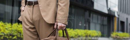 Photo pour Vue recadrée de l'homme d'affaires en costume tenant sac en cuir et debout avec la main dans la poche sur la rue urbaine, bannière - image libre de droit
